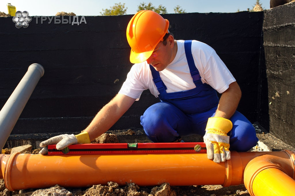 Водопроводчик, измеряющий уклон канализационных труб